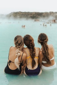 3 girls with long braided hair, wearing swimsuits, sitting in the shallow part of an aqua coloured sea, looking at an island.