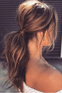 long brown hair, tied back into a low. teased ponytail, in the sunshine, bare tanned shoulders, in the street.