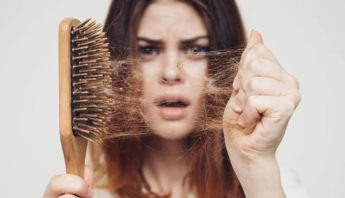 young woman anxious about post pregnancy hair loss pulling lots of hair from an hairbrush.