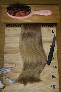 Blonde Virgin Russian hair extensions being drawn between 2 large brushes in Manchester salon
