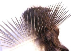 "brown hair resting on a wooden hackle with 6"" sharp silver nails"