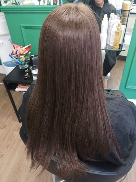 back shot of a woman with long brown hair wearing a natural looking hair integration system in Manchester salon