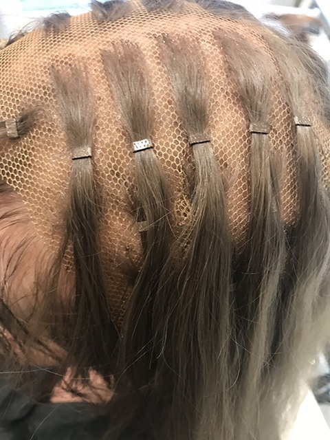 woman with hair loss being fitted with a mesh based hair integration system in Manchester