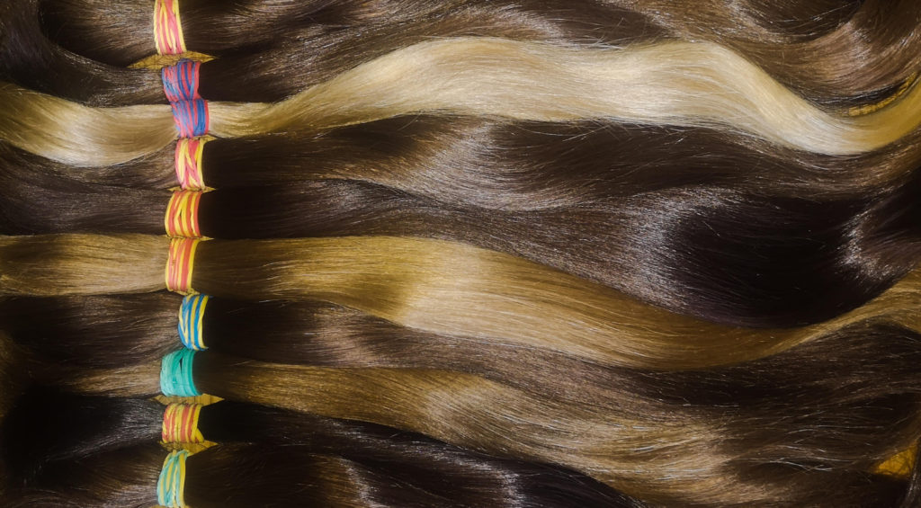 brown and blonde virgin russian hair ponytails which are used for russian hair extensions lay down and lined up in a row